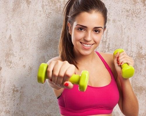 femme avec des haltères dans les mains pour éliminer les graisses