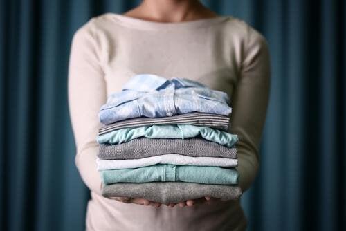 Femme qui porte une pile de vêtements