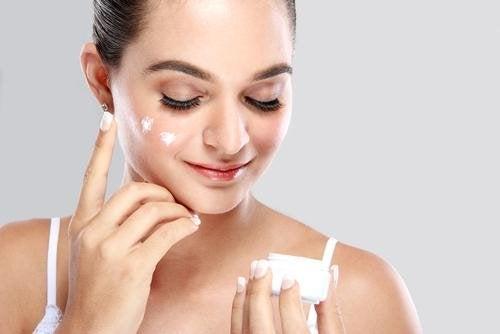 Femme qui étale de la crème sur le visage