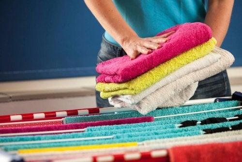 Femme qui plie les serviettes lavées avec un adoucissant maison