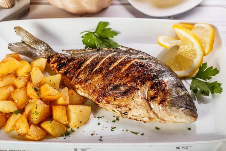Délicieux loup de mer au four avec pommes de terre et oignons