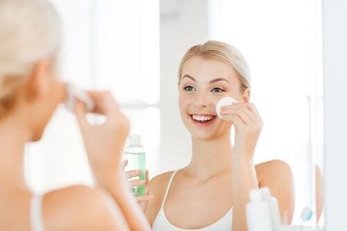 femme qui applique une lotion tonique pour avoir une peau saine et douce