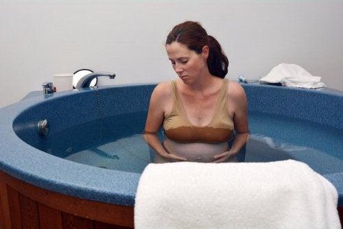 femme enceinte dans une baignoire voulant limiter les douleurs de l'accouchement