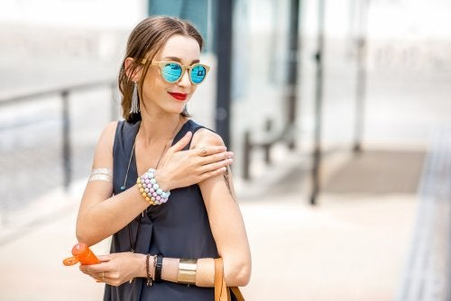 femme qui met de la crème pour éviter les taches solaires