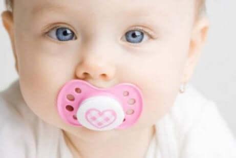 Un bébé avec sa tétine dans la bouche