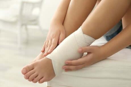 Une femme qui réalise un bandage pour remédier aux chevilles enflées