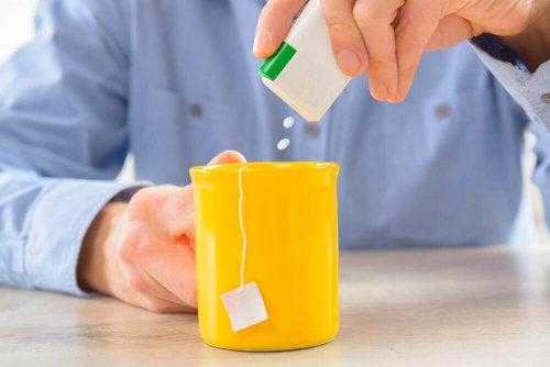 Un homme choisissant les édulcorants pour sucrer son thé