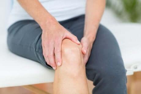 Un homme se masse le genou pour soulager les douleurs articulaires