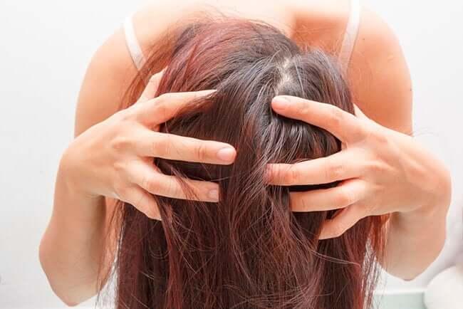 Une femme se massant les cheveux avec une de nos préparations au romarin