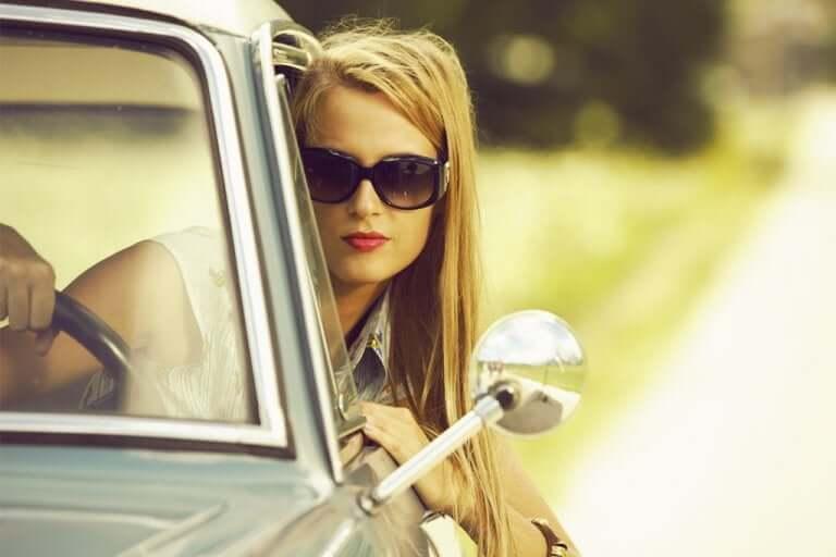Une femme conduisant avec des lunettes de soleil
