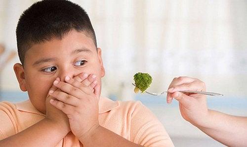 Un enfant se couvre la bouche en signe de dégoût