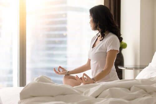Une femme qui a adopté une habitude saine et qui médite dans son lit