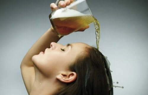 Une femme se versant de la bière sur les cheveux