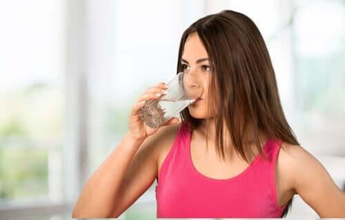Une femme en train de s'hydrater pour éviter la constipation chronique