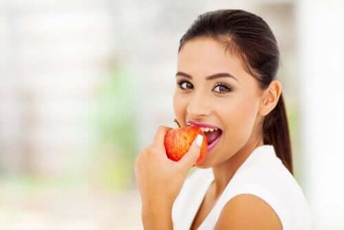Une femme croquant dans une pomme pleine de pectine