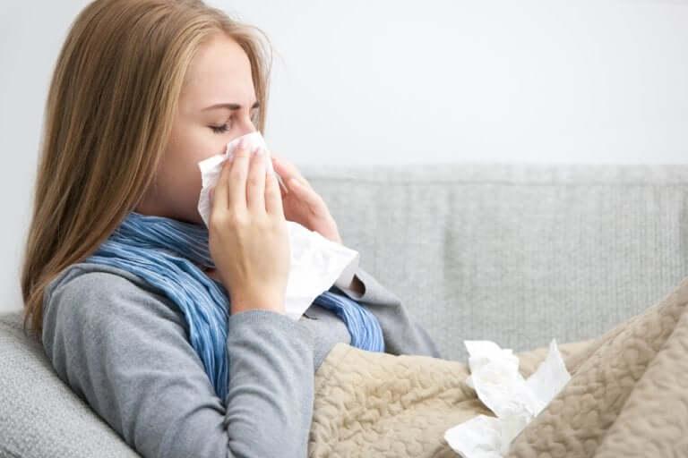 Une femme allongée se mouchant à cause d'un rhume