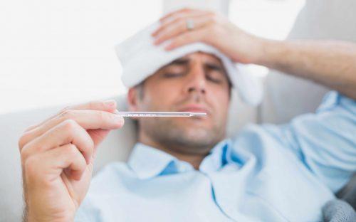 Un homme ayant la grippe prenant sa température