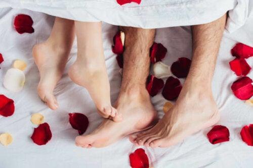 Un couple dans un lit couvert de pétales de roses pour sa nuit de noces