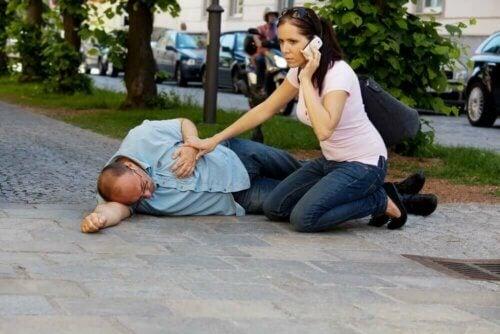 Une femme portant secours à un homme qui a fait un AVC