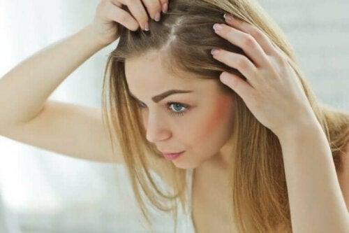 Une femme qui cherche si elle a des cheveux gris