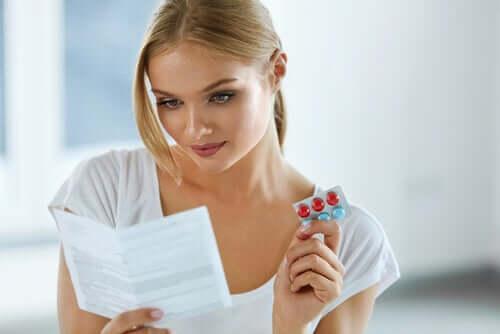 Une femme lisant les effets indésirables d'un médicament
