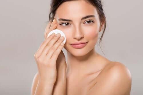 Une femme qui se nettoie le visage avec un coton avant un maquillage naturel