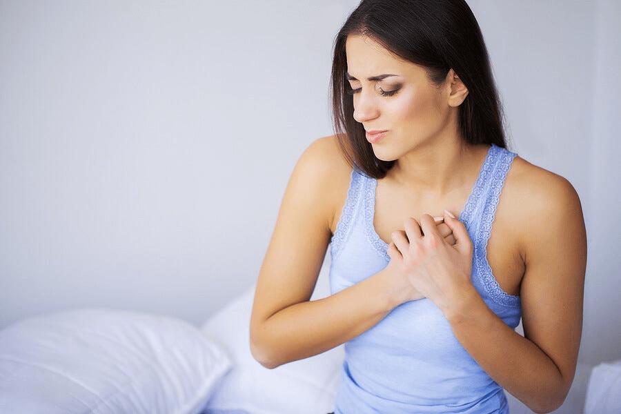 Une femme qui a mal dans la poitrine à cause d'une sensation d'essouflement
