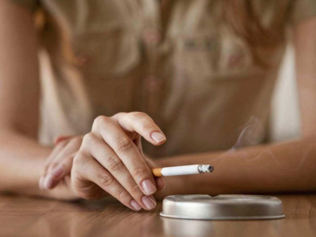 Une femme en train de fumer, ce qui a un impact sur sa santé respiratoire