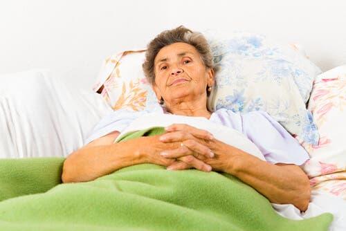 Une femme âgée couchée sur son lit ayant un mauvais rythme du sommeil