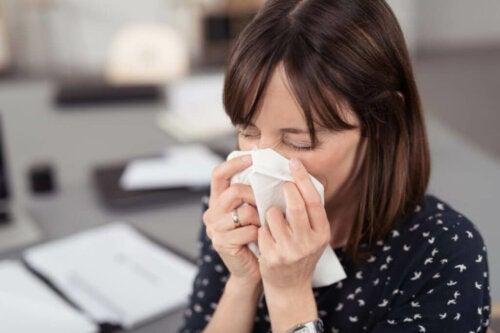 Une femme qui se mouche du fait de réactions allergiques