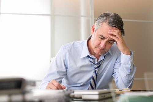 Un homme stressé au travail ayant des cheveux blancs
