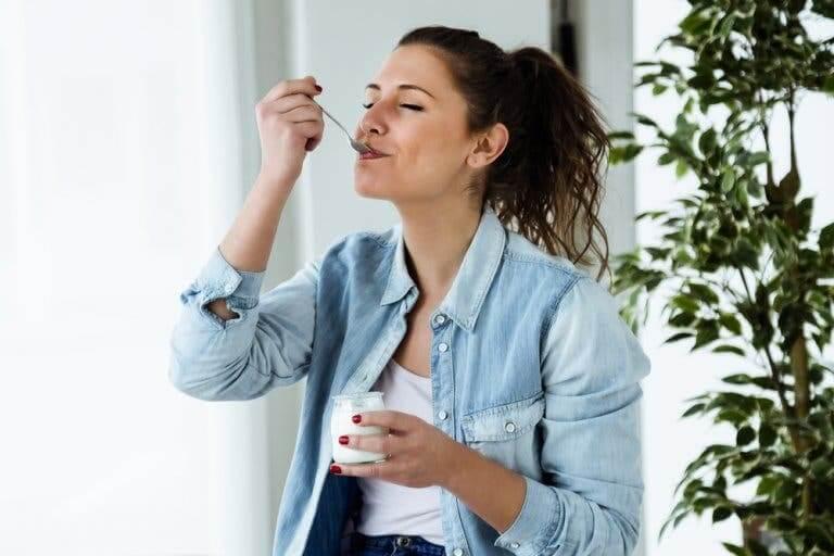 Une femme mangeant un yaourt pour apaiser la vaginose bactérienne