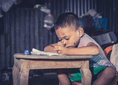 Un jeune garçon en train d'écrire sur une table