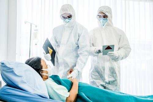 Des médecins qui portent des EPI examinant un patient