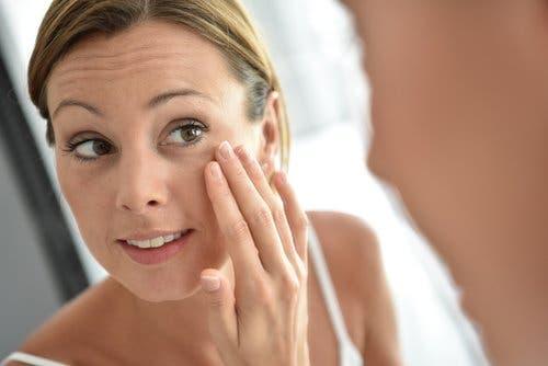 Une femme appplique de la crème au collagène sur son visage pour réduire la présence des rides