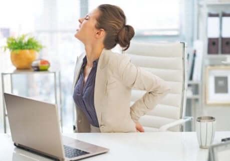 Une femme assise au bureau qui a mal au dos à cause de la discopathie dégénérative