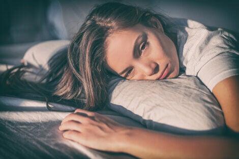 Une femme pensive et triste dans son lit souffrant de dysfonction sexuelle féminine