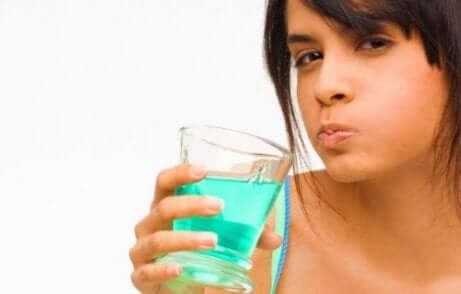 Une femme faisant un bain de bouche avec de la chlorhexidine.