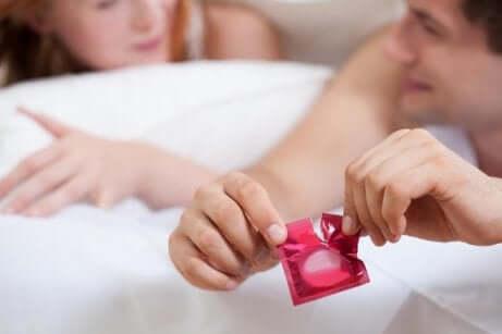 Un couple au lit avec un préservatif.