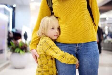 Un enfant timide collé à sa maman.
