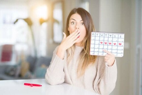 Une femme tenant un calendrier pour savoir quand est-ce qu'elle va ovuler.