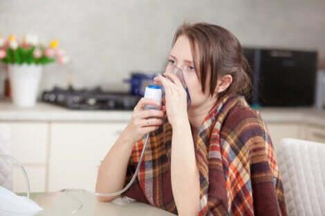 Une femme qui respire à travers un aérosol pour lutter contre les bactéries dans les poumons.