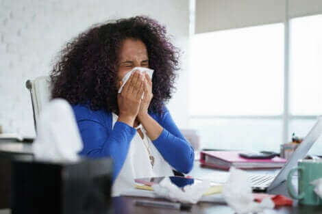 Une femme qui se mouche touchée par la grippe.