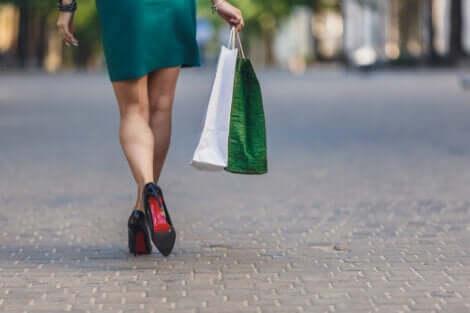 Une femme victime de dépendance au shopping qui marche avec des sacs dans la main.