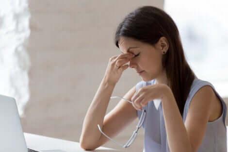 Une jeune femme qui fait du télétravail, se frotte les yeux.
