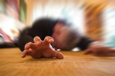 Une personne allongée qui fait une crise d'épilepsie.