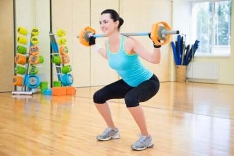 Une femme qui fait des squats avec des poids.