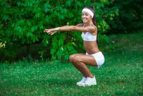 Une femme qui fait des squats en plein air.