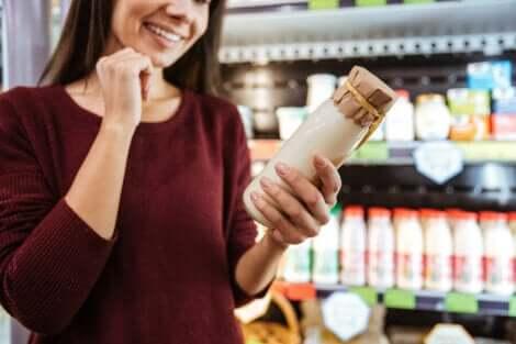 Une femme qui choisit un yaourt au supermarché.