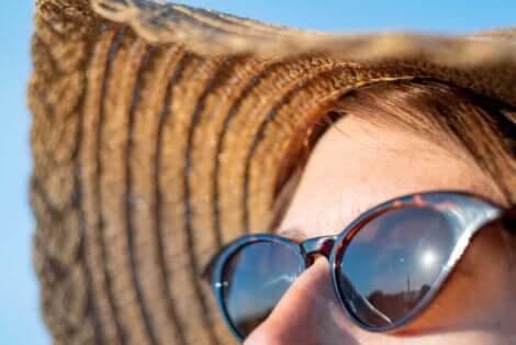 Le visage d'une femme au soleil avec des lunettes et un chapeau pour se protéger de la radiation solaire.
